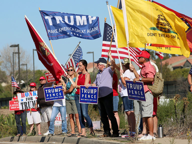 Demonstrators hold signs in support of President-elect Donald Trump outside of Camp Pendleton in Oceanside, Calif., on Nov. 11, 2016. Photo by Sandy Huffaker/Reuters