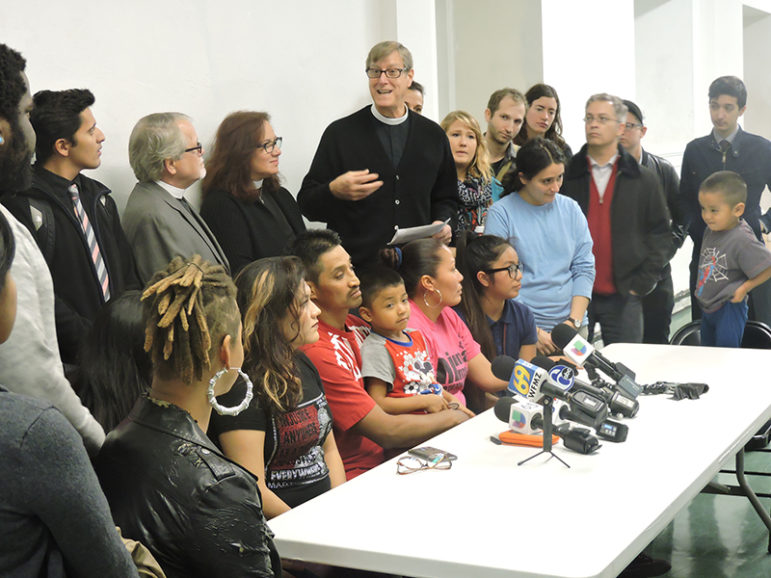 Supporters surround Javier Flores and his family during a press conference in the basement of Arch Street United Methodist Church in Philadelphia on Nov. 15, 2016. The group gathered to announce that Flores has taken asylum in the church. Senior pastor Robin Hynicka stands immediately behind him. RNS photo by Elizabeth Evans