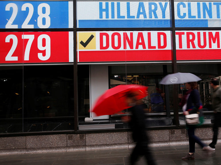 People walk by an electronic billboard in New York on Nov. 9, 2016. Photo courtesy of Reuters/Shannon Stapleton