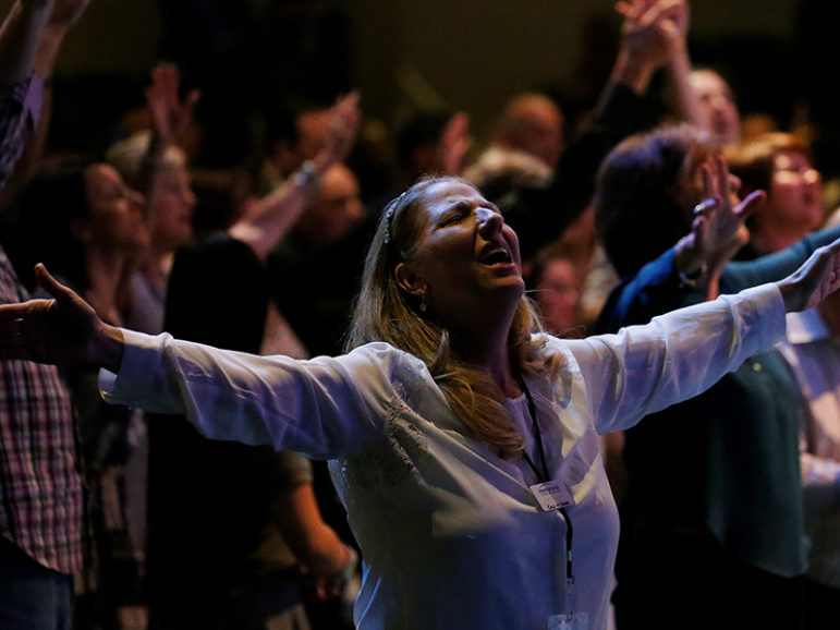 A woman prays in the room with Republican presidential nominee Donald Trump during a church service at the International Church of Las Vegas on Oct. 30, 2016. Photo courtesy of Reuters/Carlo Allegri