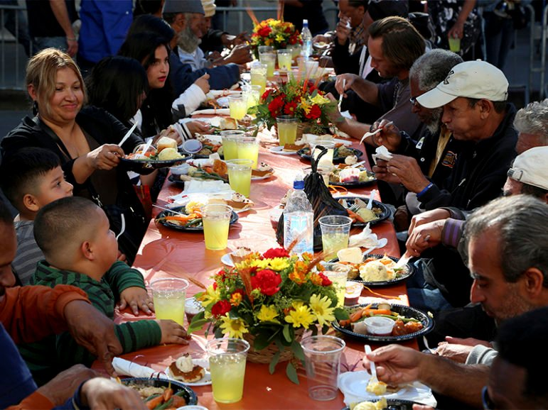 People sit down for an early Thanksgiving meal served to the homeless and others at Los Angeles Mission on skid row in Los Angeles, California on Nov. 27, 2013. More than 3,500 meals were served to those in need.  Photo courtesy of REUTERS/Jonathan Alcorn