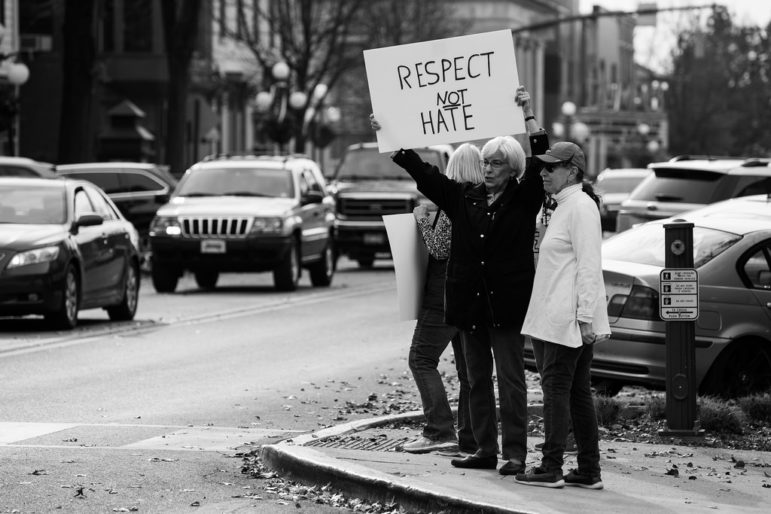 """A woman holds a sign reading """"respect not hate"""" at a November 19 community rally against racism and hate held in response to racist literature distributed near the campus of Bucknell University in Lewisburg, PA. 