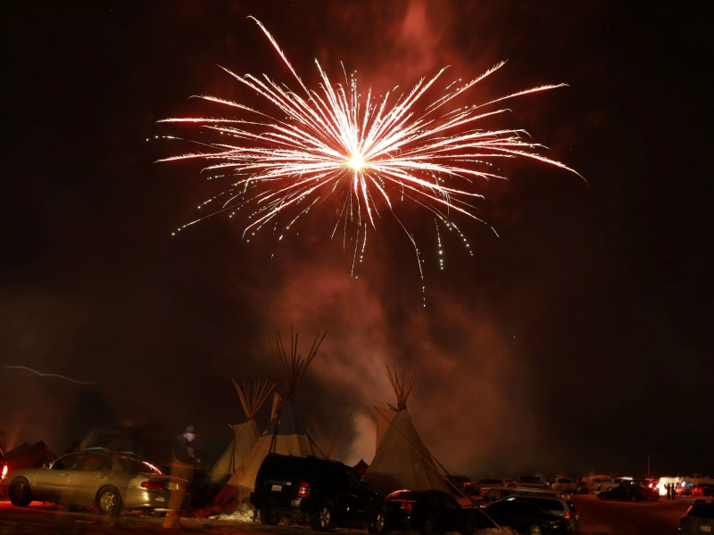 Fireworks explode above tipis