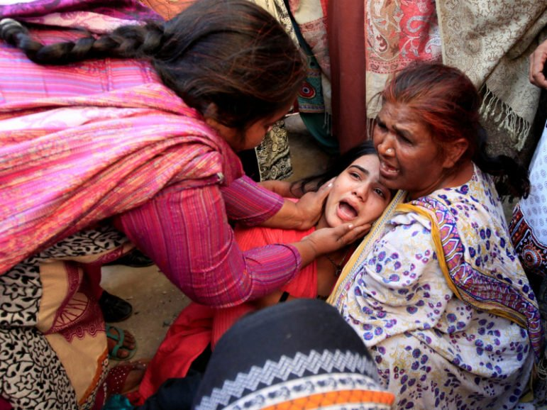 A woman is comfored by other, as she mourns the death of a relative, who died after consuming locally made toxic liquor, in Toba Tek Singh, Pakistan, December 27, 2016. REUTERS/Fayyaz Hussain