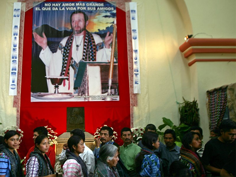 Catholics walk past a picture of Father Stanley Rother during a memorial mass in the small town of Santiago Atitlan, Guatemala, on July 28, 2006. Rother was an Oaklahoman priest killed on July 28, 1981, for his work with indigenous poor during Guatemala's brutal civil war. Photo courtesy of REUTERS/Daniel LeClair