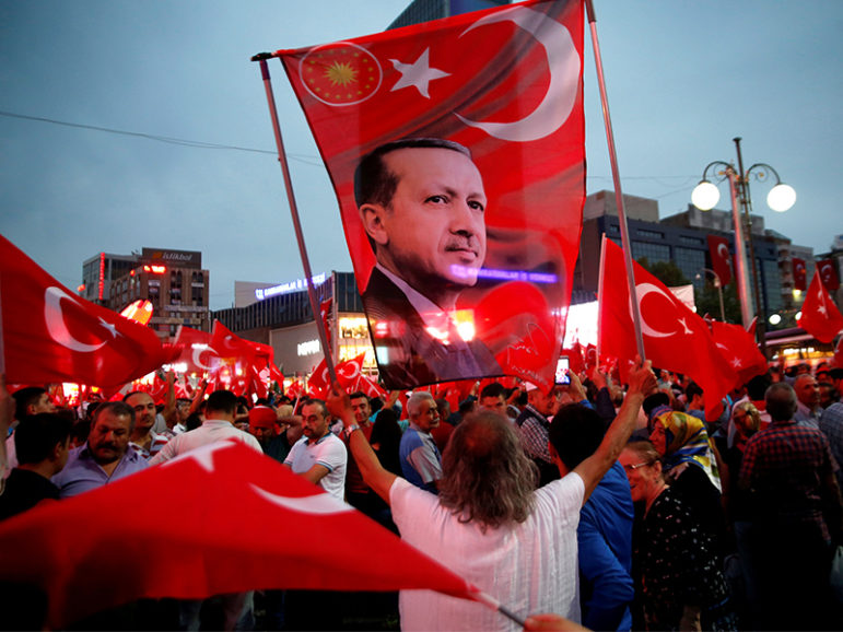 A supporter holds a flag depicting Turkish President Tayyip Erdogan during a pro-government demonstration in Ankara, Turkey, on July 20, 2016. Photo courtesy of Reuters/Baz Ratner