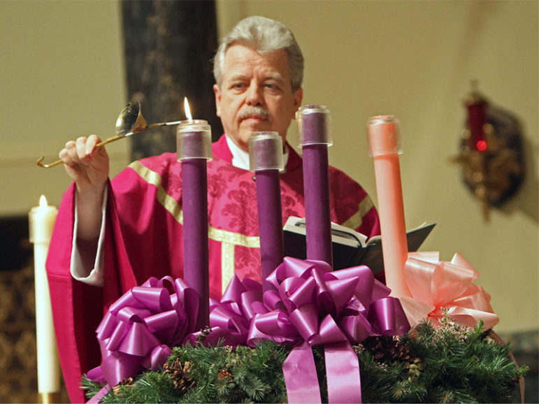 The Rev.  Joseph Schlafer lights the first candle in an Advent wreath at St. Joseph Church in Garden City, N.Y.  RNS photo by Gregory A. Shemitz.