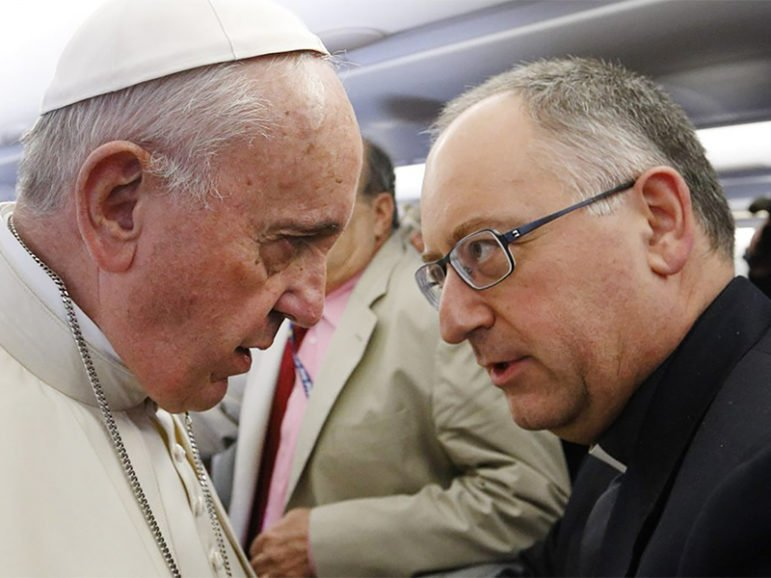 Pope Francis talks with the Rev. Antonio Spadaro, editor of La Civiltà Cattolica, as he meets journalists aboard his flight from Rome to Nairobi, Kenya, on Nov. 25, 2015.  Photo by Paul Haring, courtesy of Catholic News Service