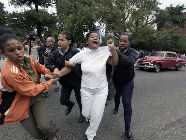 Cuban security personnel detain a member of the Ladies in White group during a protest on International Human Rights Day, in Havana, Cuba, on Dec. 10, 2014. Photo courtesy of Reuters/Enrique De La Osa