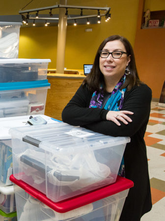 """Pastor Marta Gilliland poses with some of the Welcome Kits being collected by the Lakeland Community Church redemptive community """"Welcoming the Stranger,"""" which Gilliland helped start. RNS photo by Kit Doyle"""