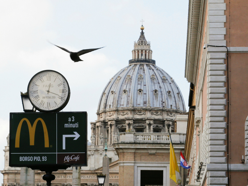 A sign in front of St. Peter's Basilica points to the newest McDonald's restaurant in Rome, next to the Vatican. Jan. 3, 2017. Photo via Reuters/Alessandro Bianchi