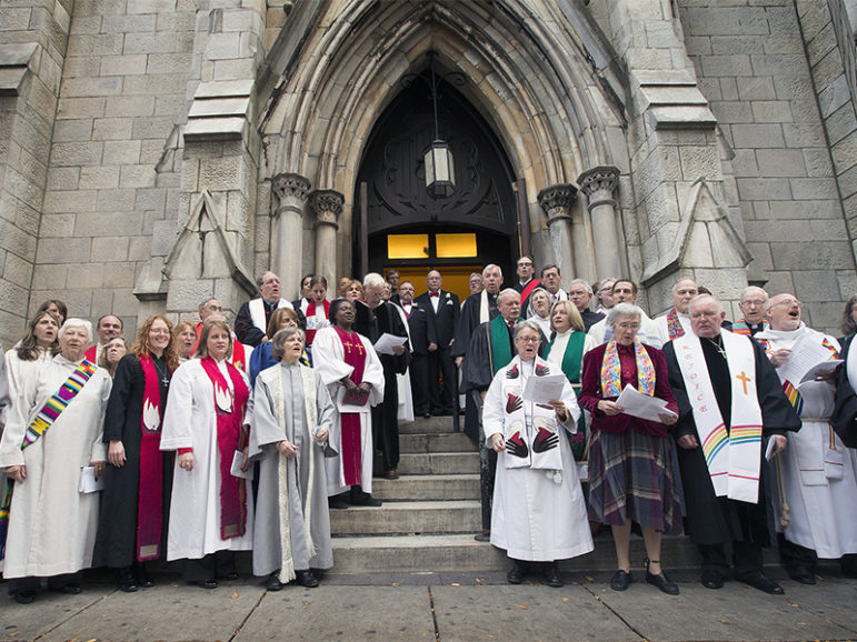 Clergy and faith leaders gather outside Arch Street United Methodist Church in Philadelphia in support of  Richard Taylor and William Gatewood (at top of stairs in doorway) after their wedding. Photo courtesy of Mike DuBose/United Methodist News Service