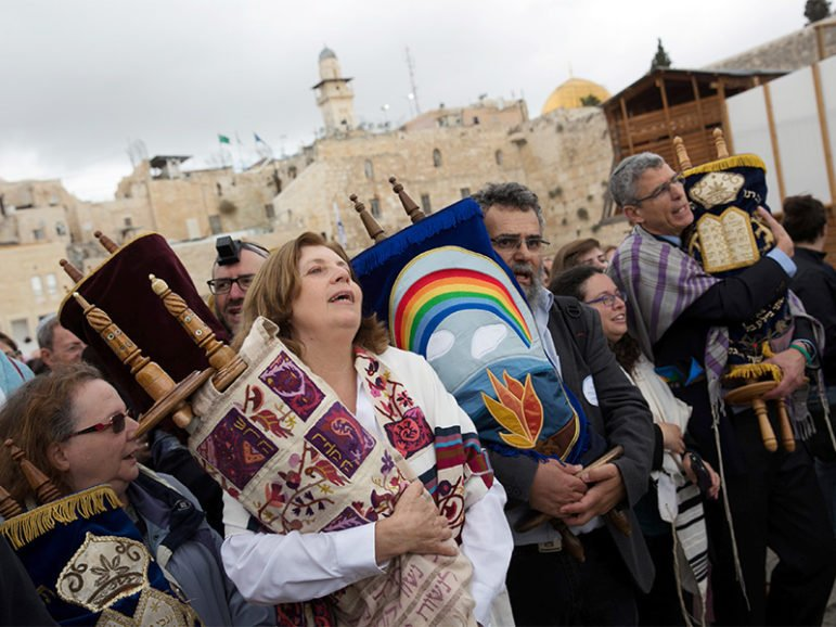 Anat Hoffman (second from left in foreground), chair of Women of the Wall, an activist group that is challenging the Orthodox monopoly over rites at the Western Wall, holds a Torah scroll during a monthly prayer at the site on Nov. 2, 2016. The Western Wall is Judaism's holiest prayer site. Photo courtesy of Reuters/Michal Fattal