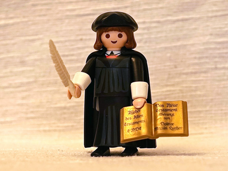 """Playmobil's toy figure of Martin Luther, in its trademark style aimed at children up to 12 years old. The word """"Ende"""" (End) at the bottom of the left page of the Bible raised objections that the toy could be anti-Semitic. Photo taken Dec. 31, 2016. RNS photo by Tom Heneghan"""
