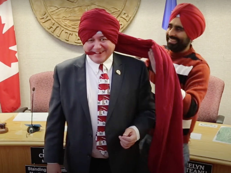 The video of writer Gurdeep Pandher, right, teaching Mayor Dan Curtis how to wear a Sikh turban has gone viral from the town of Whitehorse, the Yukon Territory capital, in northwest Canada.  Screenshot from video