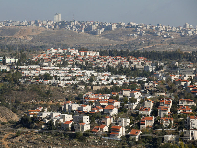 Houses are seen in the Israeli settlement of Givat Zeev (bottom) with the Palestinian city of Ramallah in the backgraund, in the occupied West Bank, on Dec. 29, 2016. Photo courtesy of Reuters/Baz Ratner