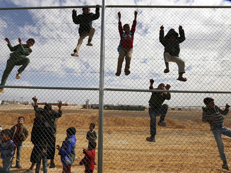 Syrian refugee children climb on a fence to watch a football training workshop in a refugee camp to provide Syrian and Jordanian trainers with football training skills, at Azraq refugee camp near Al Azraq city, Jordan, on Nov. 16, 2015. Photo courtesy of Reuters/Muhammad Hamed *Editors: This photo may only be republished with RNS-TRUMP-REFUGEES, originally transmitted on Jan. 25, 2017.