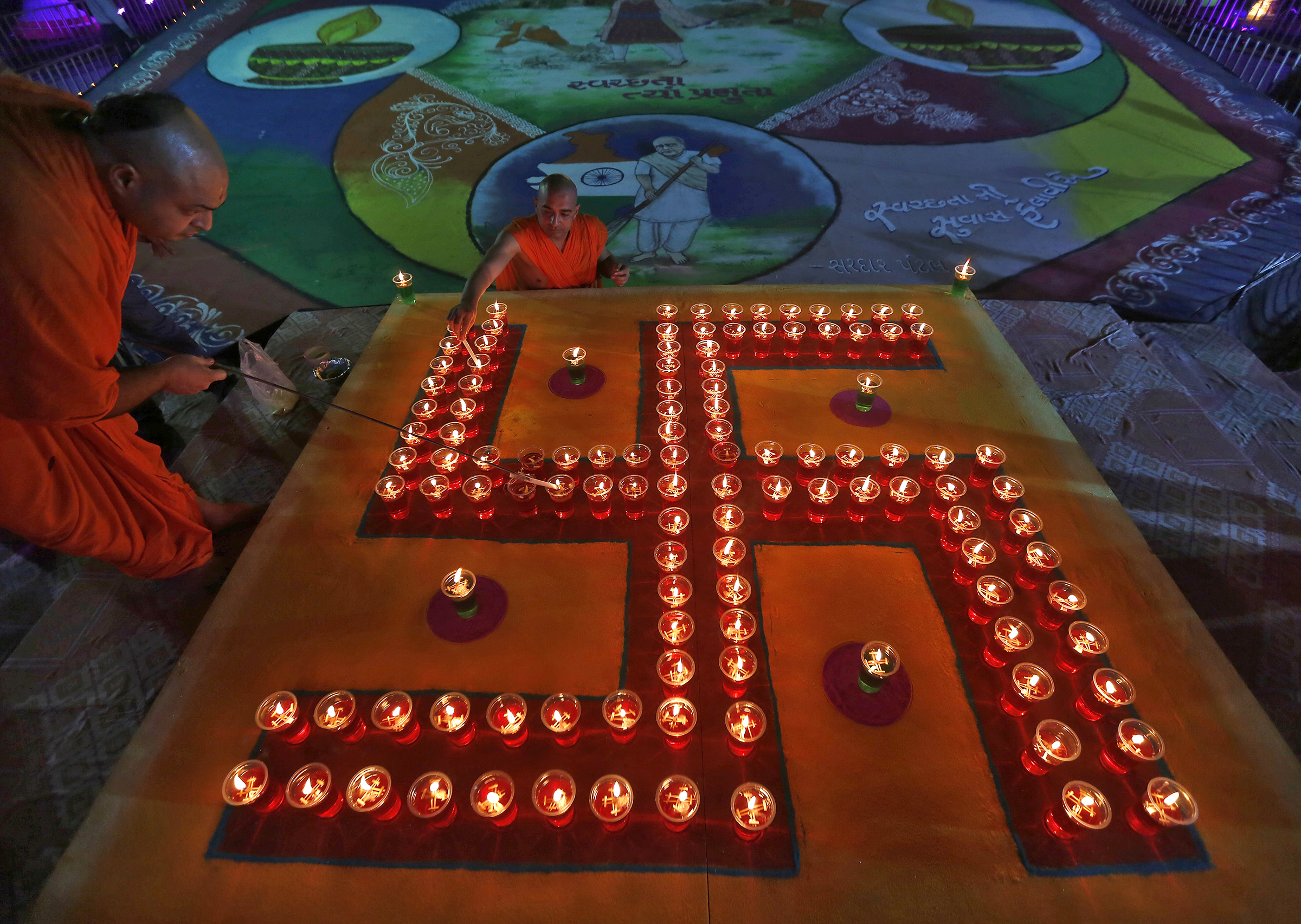 PRINT Hindu priests light oil lamps in a formation of the