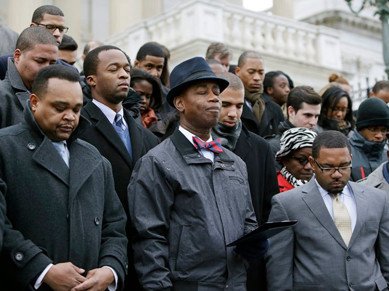 African-American congressional staffers and representatives stage a walkout on the steps of the House of Representatives at the U.S. Capitol in Washington on Dec. 11, 2014 to protest the deaths of Michael Brown and Eric Garner. Senate Chaplain Barry Black, center, leads the group in prayer. Photo courtesy of REUTERS/Gary Cameron