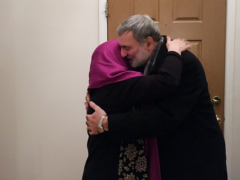 """Mohsen Kadivar and his wife, Zahra """"Nikoo"""" Roodi, embrace at the door of their Chapel Hill, N.C., home on Feb. 16, 2017. Kadivar had to cut short a Berlin fellowship because of President Trump's travel ban. RNS photo by Yonat Shimron"""