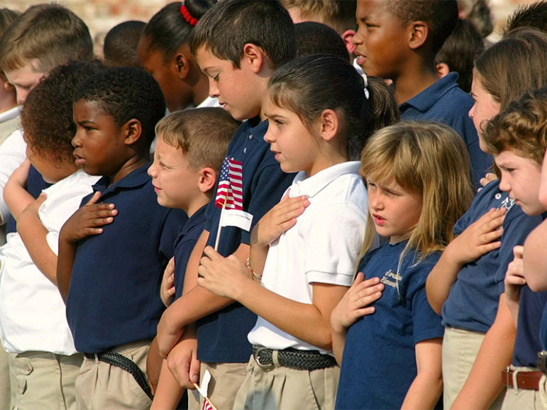 Students from an Alabama elementary school choir place their hands over their hearts during the recitation of the Pledge of Allegiance in 2003. Photo by Mary Hattler