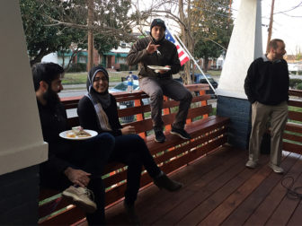 At the opening ceremony for the Light House in Raleigh, N.C., a group of young Muslims hung out on the porch eating Middle Eastern food. RNS photo by Yonat Shimron
