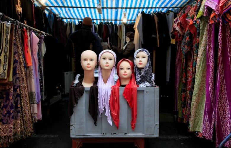 People look at a market stall selling the hijab