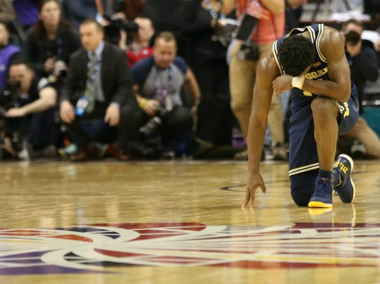 Michigan Wolverines guard Derrick Walton Jr. kneels on the court at the conclusion of the Wolverines' game against the Wisconsin Badgers during the Big Ten Conference Tournament championship game March 12, 2017, at Verizon Center in Washington, D.C. The Wolverines won 71-56. Photo via Geoff Burke-USA TODAY Sports