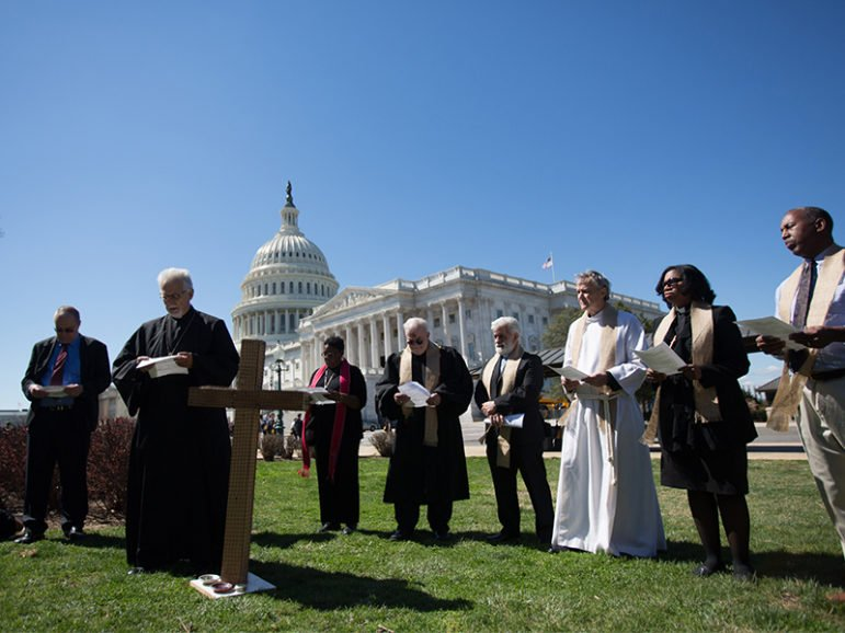 Christian leaders pray and protest the federal budget cuts President Trump has proposed outside the U.S. Capitol on March 29, 2017.  Photo courtesy of Joseph Molieri/Bread for the World