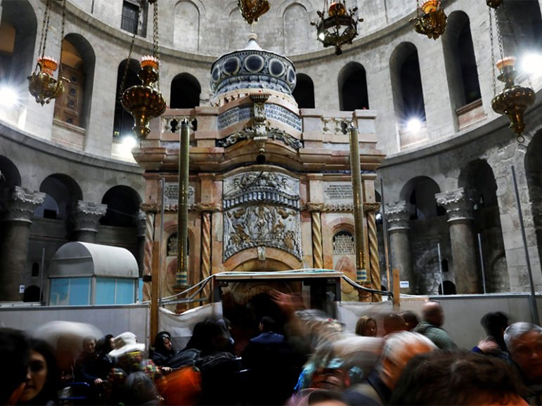 Visitors stand near the newly restored Edicule, the ancient structure housing the tomb, which according to Christian belief is where Jesus's body was anointed and buried, seen at the completion of months of restoration work at the Church of the Holy Sepulchre in Jerusalem's Old City on March 20, 2017. Photo courtesy of Reuters/Ronen Zvulun