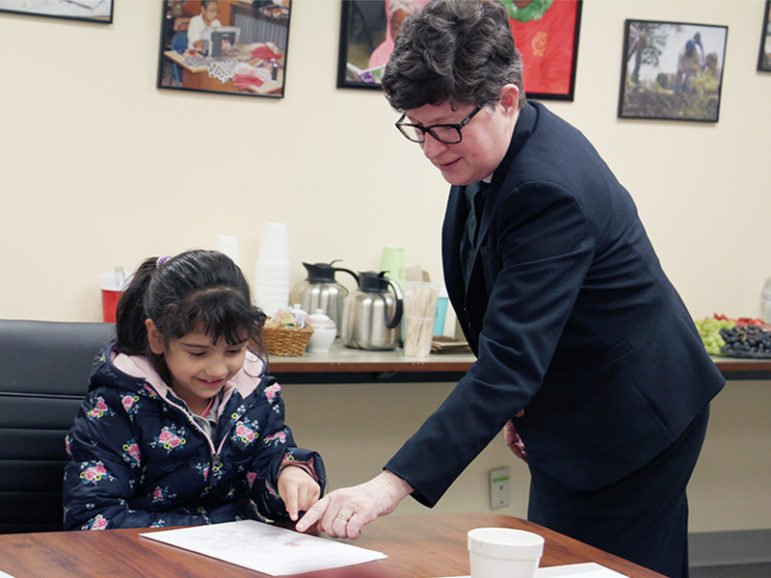 The Rev. Elizabeth A. Eaton, presiding bishop of the Evangelical Lutheran Church in America, talks with Dalal, a 6-year-old refugee from Syria, about her artwork at RefugeeOne on March 21, 2017, in Chicago. RNS photo by Emily McFarlan Miller