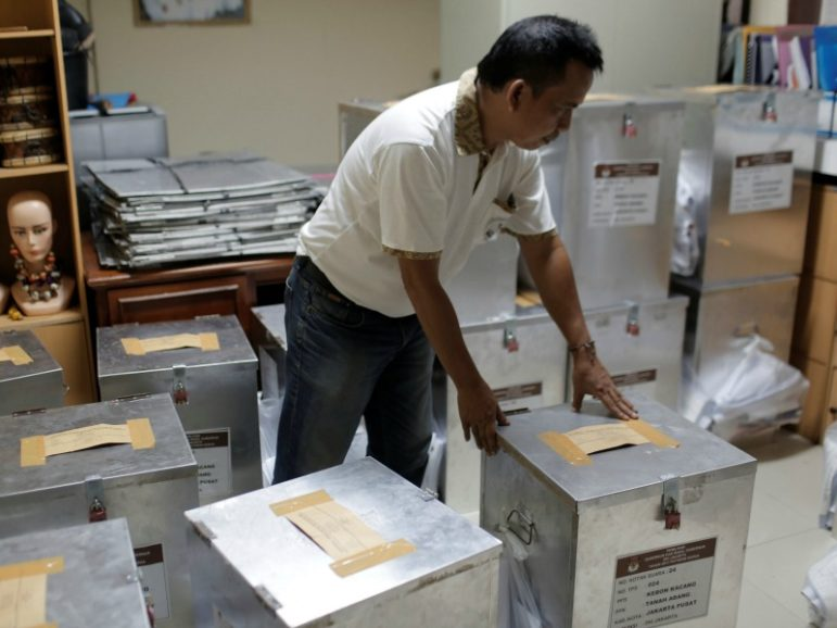 An election official prepares ballot boxes before distributing them to polling stations on April 18, 2017, in Jakarta, Indonesia. Photo by Beawiharta/Reuters