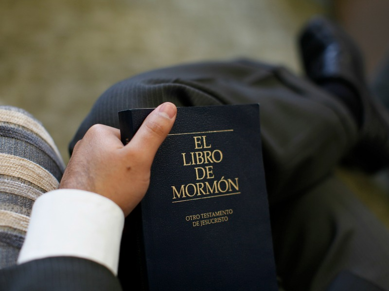 A Mormon holds a copy of The Book of Mormon