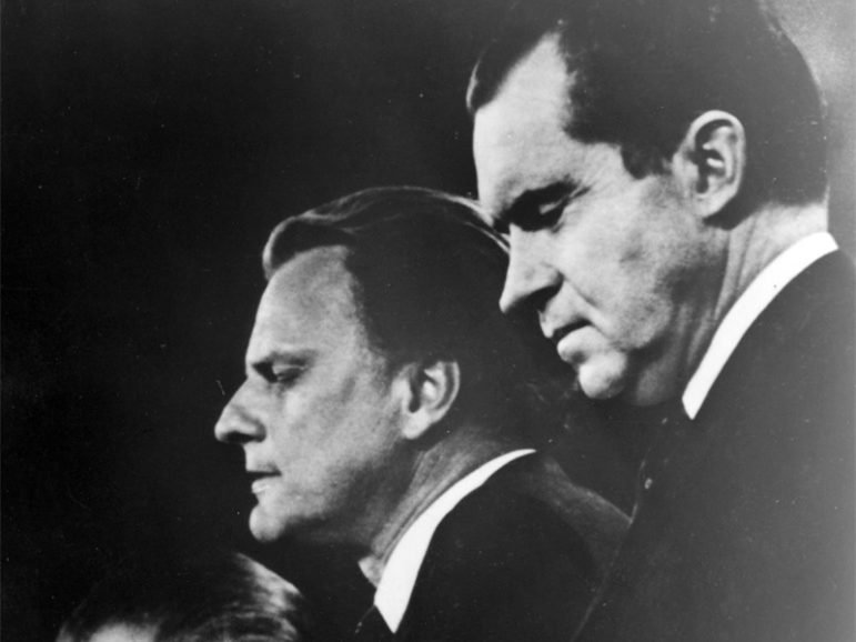 Evangelist Billy Graham, center, is flanked by GOP Presidential candidate Richard Nixon, right, and Gov. Spiro T. Agnew, the vice-presidential choice, left, as he delivers the benediction at the Republican National Convention in Miami Beach in 1968. Mr. Graham prayed for the unity and welfare of the nation. Religion News Service file photo.