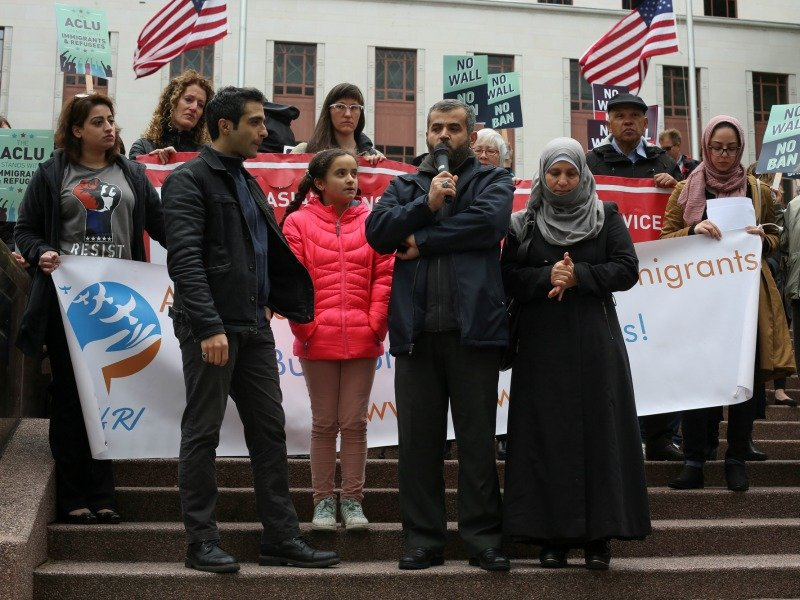 Mustafa Al-Mustafa, center right, a refugee from Syria, speaks with the help of a translator, Moh Kilani, left, while joined by his wife, Jamila Al-Mustafa, right, and daughter, Yamama, 11, center left, during a protest against President Trump's travel ban outside of the U.S. Court of Appeals on May 15, 2017, in Seattle. Photo courtesy of Reuters/David Ryder