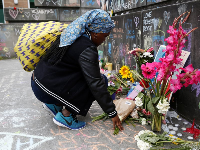 A Muslim woman, who preferred not to give her name, prays on May 29, 2017, at a makeshift memorial in Portland, Ore., for two men who were killed on a commuter train while trying to stop another man from harassing two young women who appeared to be Muslim. Photo courtesy of Reuters/Terray Sylvester