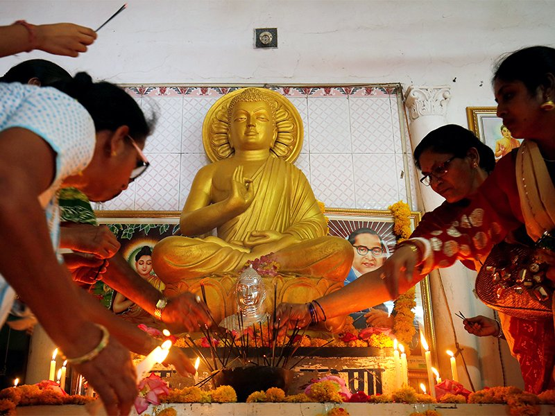 Women light candles in front of a Buddha statue inside a temple on the occasion of Buddha Purnima festival, also known as Vesak day, in Ahmedabad, India, on May 10, 2017. Photo courtesy of Reuters/Amit Dave