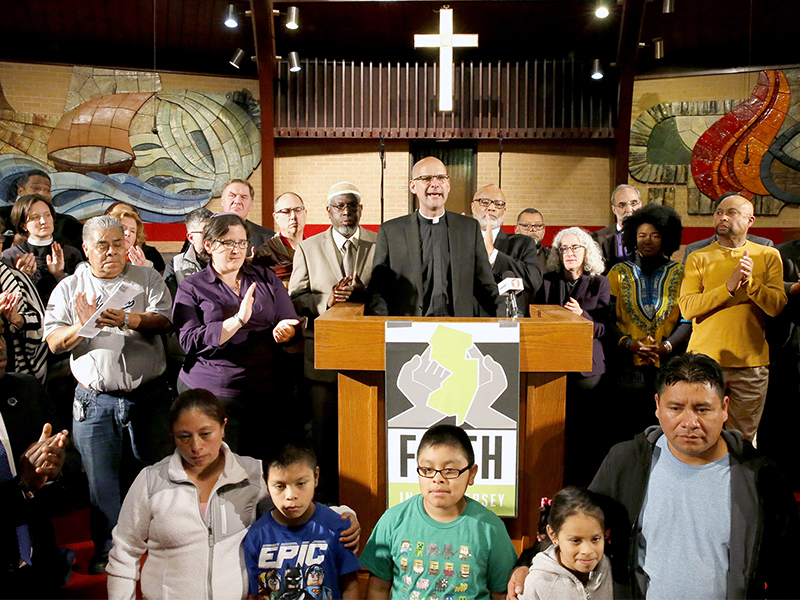 At the end of the program the Rev. John Mennell, center, invites clergy and others to come to the pulpit and stand for immigrants and to resist the deportations. More than 100 other clergy leaders stand up for immigrant rights as part of Faith in New Jersey program at Bethany Baptist Church, on May 4, 2017, in Newark, N.J. Photo courtesy of NJ Advance Media/Aristide Economopoulos