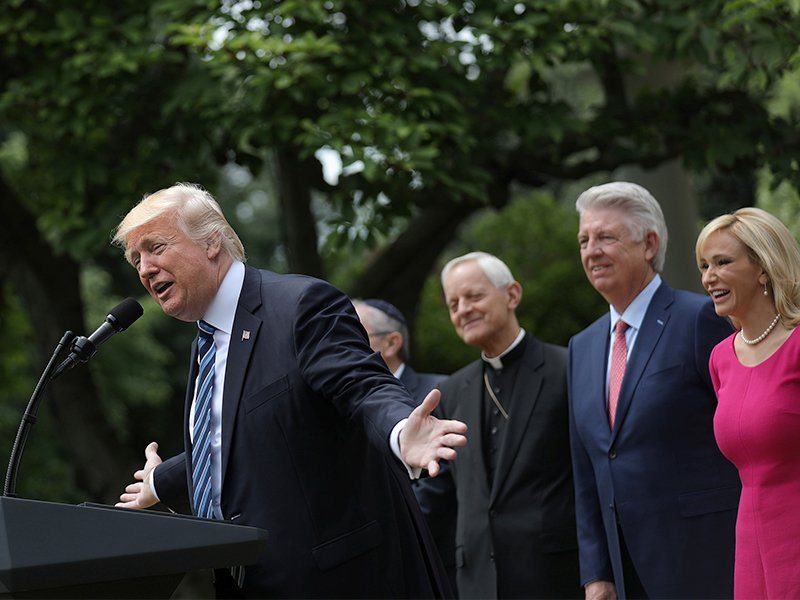 President Trump, flanked by evangelical leaders Paula White, right, and Jack Graham, in blue suit, speaks during the National Day of Prayer event at the Rose Garden of the White House in Washington, D.C., on May 4, 2017. Photo courtesy of Reuters/Carlos Barria