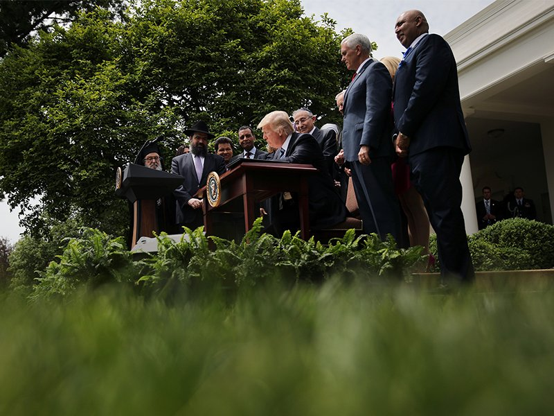 President Trump signs an Executive Order on Promoting Free Speech and Religious Liberty during the National Day of Prayer event at the Rose Garden of the White House in Washington, D.C., on May 4, 2017. Photo courtesy of Reuters/Carlos Barria