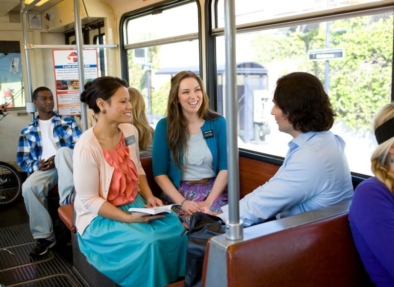Two sister missionaries talk with a man on a train. Photo courtesy of Intellectual Reserve, Inc.