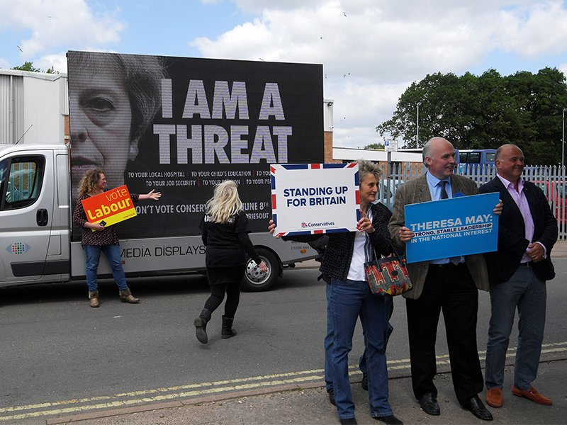 Labour Party supporters, rear, stand next to an electronic billboard behind Conservative Party supporters, front, outside a campaign event attended by Britain's Prime Minister Theresa May in Norwich, Britain, on June 7, 2017. Photo courtesy of Reuters/Toby Melville *Editors: This photo may only be republished with RNS-BRITAIN-ELECTION, originally transmitted on June 7, 2017.