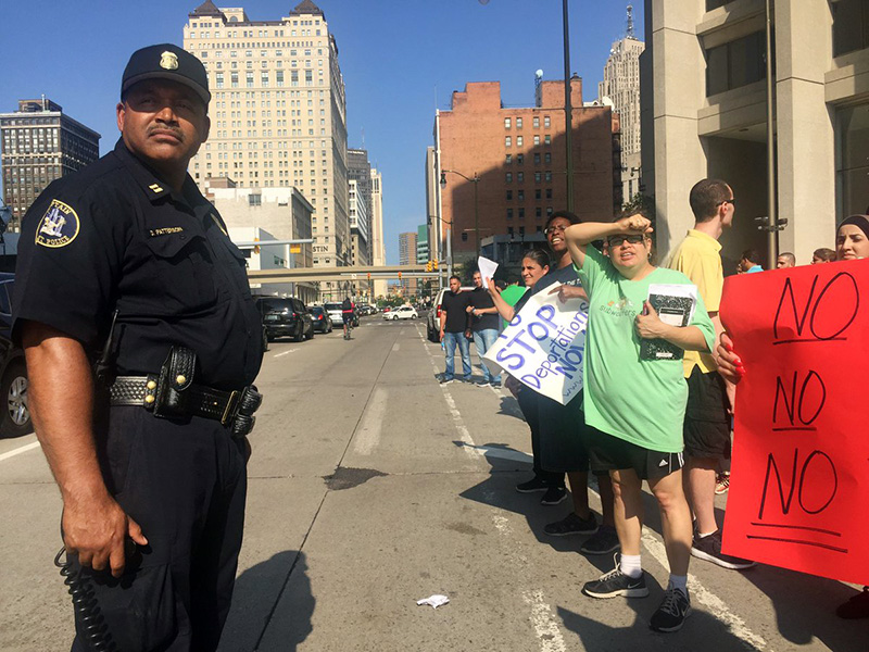 Detroit Police Capt. Darrell Patterson stands between deportation protesters and traffic in downtown Detroit. Photo courtesy of Detroit Free Press/Allie Gross