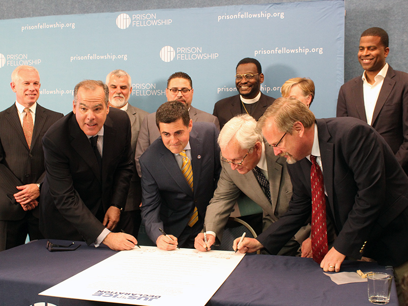 """Leaders of evangelical organizations sign the """"Justice Declaration,"""" a statement by Christian leaders on criminal justice reform, in Washington, D.C., on June 20, 2017. Left to right in foreground, Prison Fellowship Ministries President James Ackerman, Southern Baptist ethicist Russell Moore, National Association of Evangelicals President Leith Anderson and David Carlson, of the Colson Center for Christian Worldview. RNS photo by Adelle M. Banks"""
