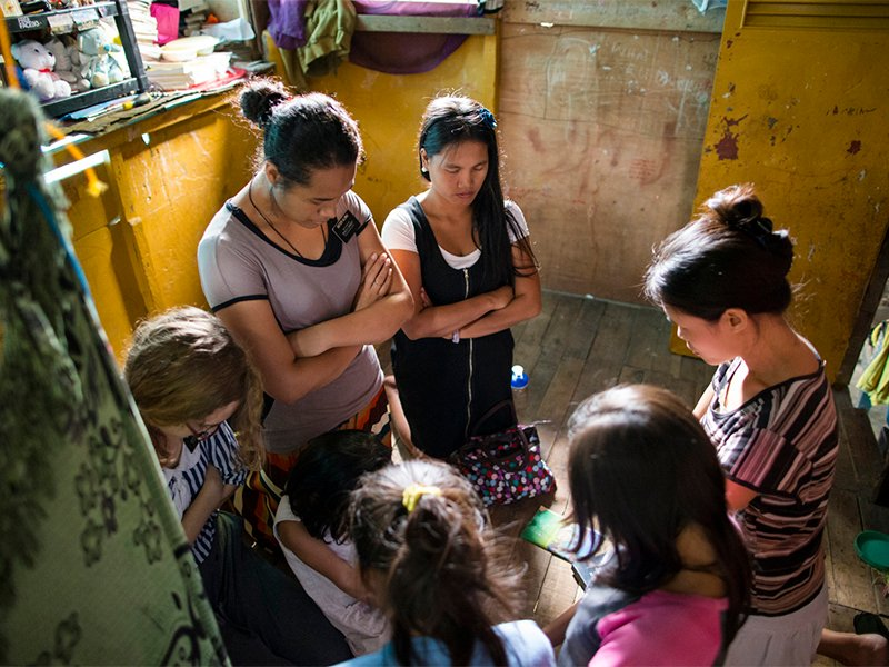 Three sister missionaries kneel in prayer with a family in the Philippines.  Photo courtesy of Intellectual Reserve, Inc.