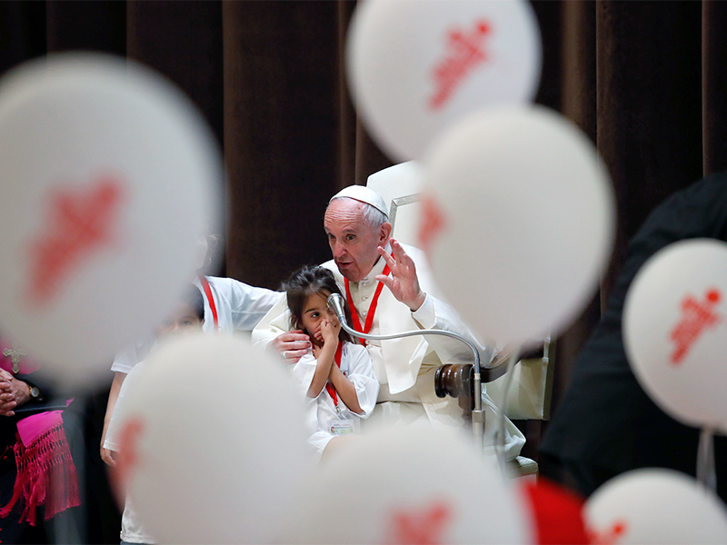 Pope Francis talks as he embraces a child during a special audience with members of the