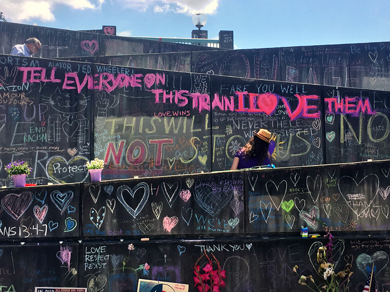 A woman traces over messages emphasizing love in chalk to make sure they do not fade on May 31, 2017, at a makeshift memorial that has sprung up outside the Hollywood Transit Station in Portland, Ore., where three men were stabbed on a train. RNS photo by Emily McFarlan Miller