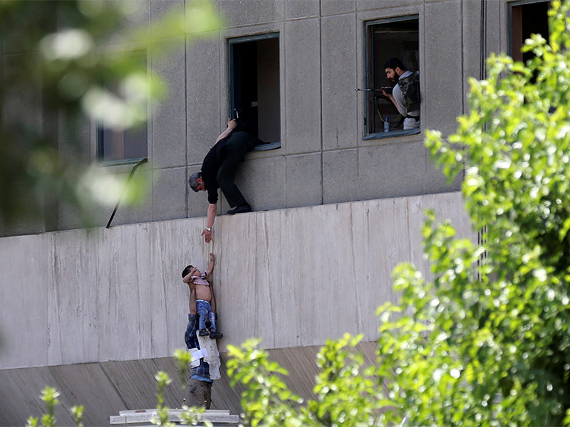 A boy is evacuated during an attack on the Iranian parliament in central Tehran, Iran, on June 7, 2017. Photo by Omid Vahabzadeh/TIMA via Reuters