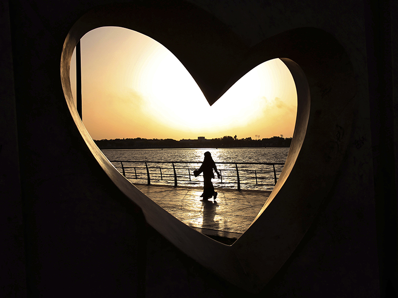 In this May 11, 2014, file photo, a Saudi woman seen through a heart-shaped statue walks along an inlet of the Red Sea in Jiddah, Saudi Arabia. A young Saudi woman has sparked a sensation online by posting a video of herself in a miniskirt and crop top walking around in public, with some Saudis calling for her arrest and others rushing to her defense. The video, first shared on Snapchat, shows her walking around an empty historic fort in Ushaiager, a village north of the capital, Riyadh, in the desert region of Najd, where many of Saudi Arabia's most conservative tribes and families are from. (AP Photo/Hasan Jamali, File)