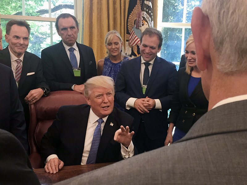 Ronnie Floyd, from left, Rodney Howard-Browne, Adonica Howard-Browne, Johnnie Moore, and Paula White stand behind President Trump as he talks with evangelical supporters in the Oval Office at the White House.  Photo courtesy of Johnnie Moore